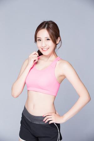 Sport meisje op een grijze achtergrond. Running fitness sport vrouw lachend blij. Aziatische schoonheid