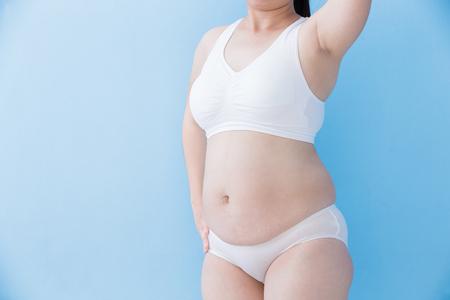 mujeres gordas: La grasa corporal mujer con sobrepeso con el fondo azul, asiático