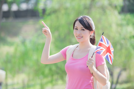 british girl: Happy College Student girl hold British flag and show something with nature white background, asian