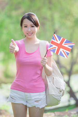 british girl: Happy College Student girl hold British flag and show thumb up with nature white background, asian
