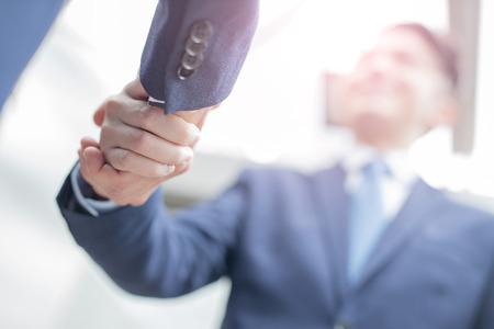 Gruppo di successo business team di stringere la mano in ufficio con sfondo di città, asiatico