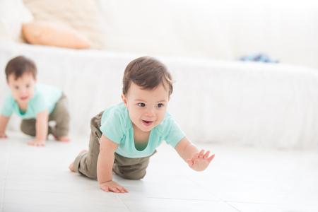 gemelos niÑo y niÑa: arrastrándose gemelo del bebé en piso de la sala, niño caucásico