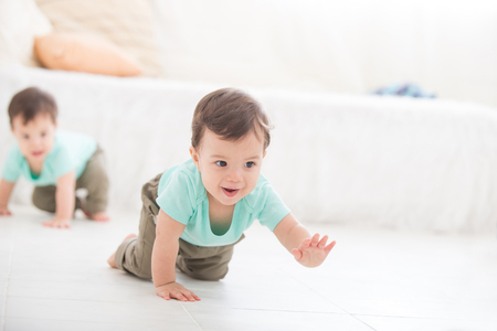 Baby, Zwilling auf dem Boden des Wohnzimmers, kaukasisch kind kriechen