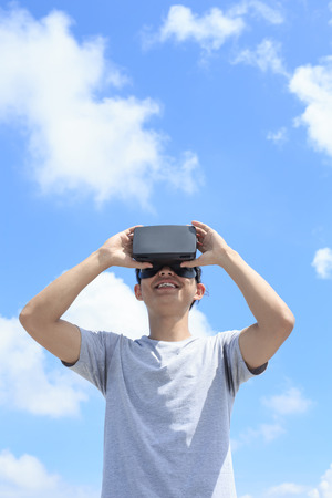 touch screen: Smile happy man getting experience using VR-headset glasses of virtual reality with sky and cloud background, asian male Stock Photo