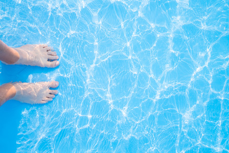 aqua naked: Barefoot and blue swimming pool rippled water background, great for your background and texture