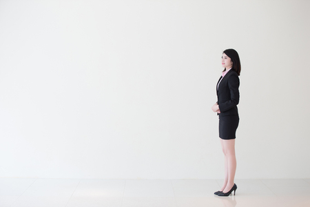 businesswoman suit: business woman look something with white wall background, great for your design or text, asian Stock Photo