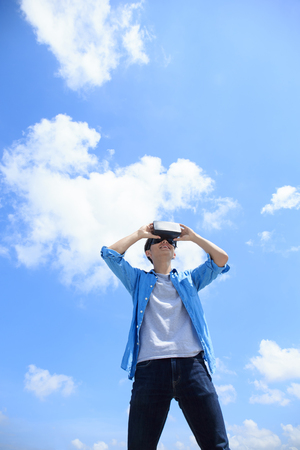 virtual reality simulator: Smile happy man getting experience using VR-headset glasses of virtual reality with sky and cloud background, asian male Stock Photo