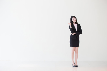 business asia: business woman show thumb up with white wall background, great for your design or text, asian