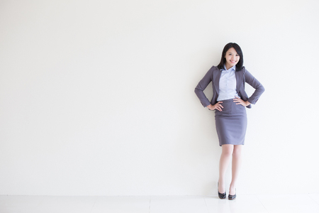 femmes souriantes: business woman stand with white wall background, great for your design or text, asian