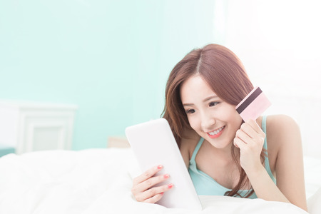business asia: smile woman shopping on internet by digital tablet pc or smart phone and she lying on the bed at home , asian girl