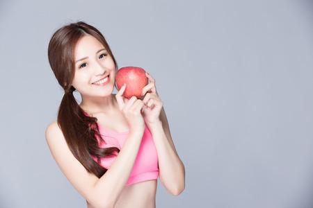 Muchacha del deporte con una manzana en la mano aisladas sobre fondo gris. Funcionamiento de la mujer de fitness deporte sonriente feliz. belleza asiática Foto de archivo
