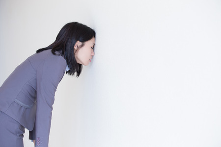 feeling: Unhappy thinking business woman with white wall background, great for your design or text, asian Stock Photo