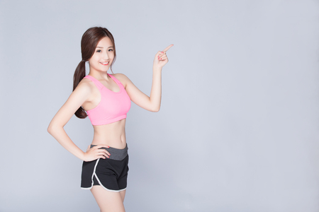 Sport girl pointing something isolated on gray background. Running fitness sport woman smiling happy. asian beauty Stock Photo