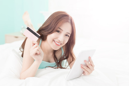 finance girl: smile woman shopping on internet by digital tablet pc or smart phone and she lying on the bed at home , asian girl