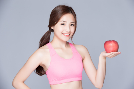 girl sport: Sport girl with an apple on her hand isolated on gray background. Running fitness sport woman smiling happy. asian beauty