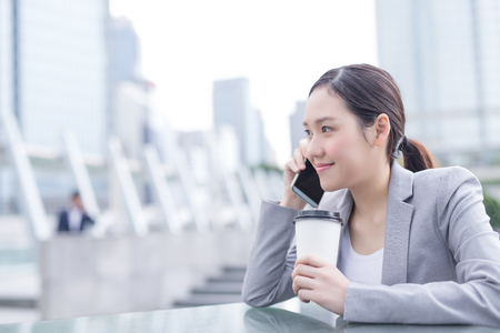 speak: business woman smile speak smart phone and hold coffee cup in office, asian beauty