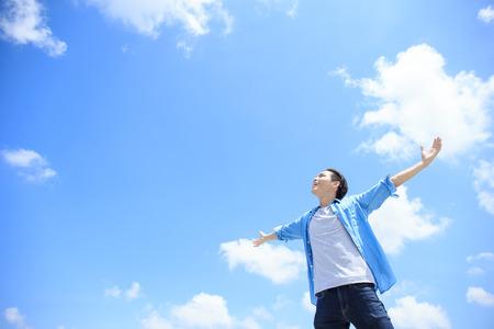 Zorgeloos en vrij man opgeheven handen en op zoek naar een hemel, aziatische Stockfoto