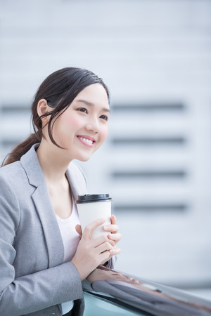 hot secretary: business woman smile and hold coffee cup with office background, asian , shot in Hong Kong Stock Photo
