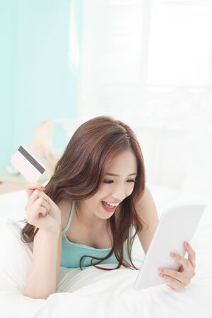 cellular: smile woman shopping on internet by digital tablet pc or smart phone and she lying on the bed at home , asian girl