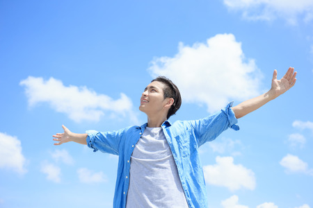 Carefree and free man raised hands and looking to a sky, asian