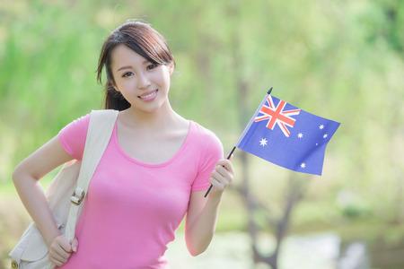 jovenes estudiantes: Feliz niña estudiante universitario mantenga bandera australiana con la naturaleza fondo blanco, asiático