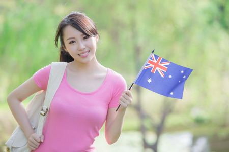 Happy College Student girl hold australian flag with nature white background, asian