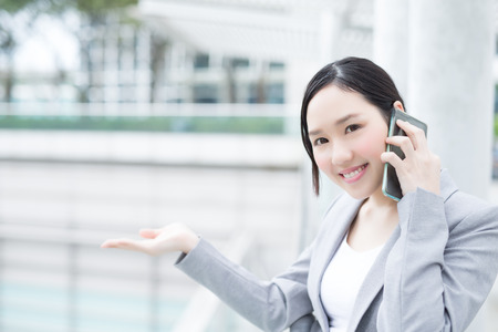 women smiling: business woman pointing show and smile speak smart phone in office, asian beauty