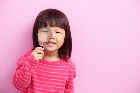 preschooler:  little girl holding magnifying pink clothes,asian