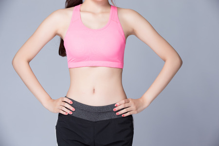arms akimbo: Cropped image of attractive young sport woman stand and akimbo islotaed on gray background