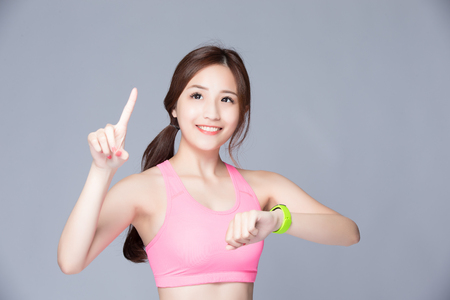 sport fitness: Happy sport smile woman look smart watch isolated on gray background, , asian beauty
