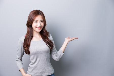 A woman dressed in winter clothing and wearing jeans show some thing with isolated gray background,asian Reklamní fotografie