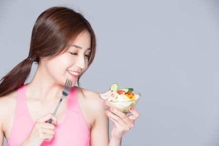 young woman eat salad and smile isolated gray background Stock Photo