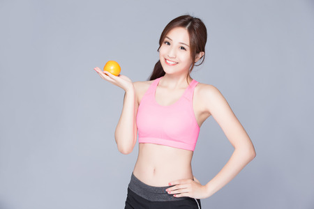 beauty and health: Happy sport Woman show orange benefit to health, asian beauty,isolated with gray background Stock Photo