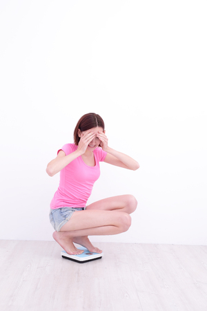 girl squatting: white girl squatting  on a scale with her hands cover her eyes Stock Photo