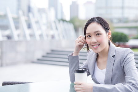 hongkong: business woman sit and hold coffee cup with office background, asian , shot in Hong Kong Stock Photo