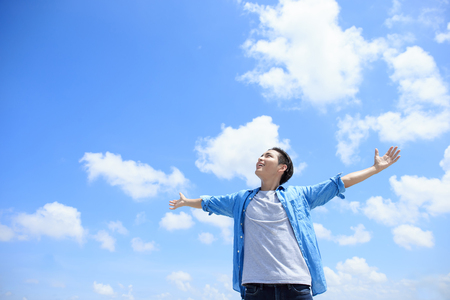 sky sun: Carefree and free man raised hands and looking to a sky, asian