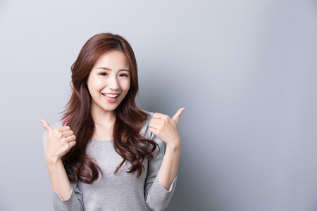 Young woman show thumb up and wearing jeans and with isolated gray background,asian