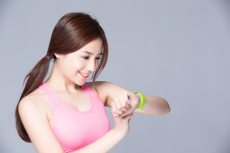 blood sport: Health sport woman wearing smart watch device isolated on gray background, asian beauty