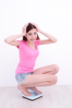en cuclillas: chica blanca en cuclillas en una escala con las manos en la cabeza Foto de archivo