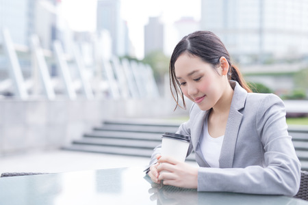 business asia: business woman sit and hold coffee cup with office background, asian , shot in Hong Kong Stock Photo