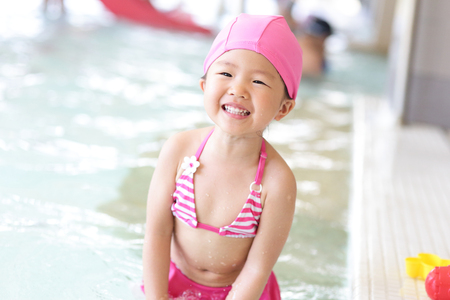 swimming costumes: little cute girl wear swimsuit play happily and exciting in the swimming pool, asian