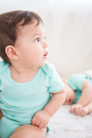baby sit: cute baby boy look somewhere and sit on the white bed in bedoom, caucasian Stock Photo