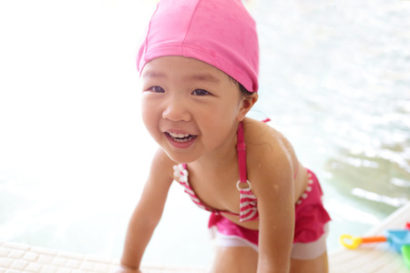 mouth cloth: little cute girl wear swimsuit play happily and exciting in the swimming pool, asian