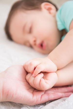 puños cerrados: Mano grande sostenga puño lindo del bebé y sueño del bebé en la cama blanca en dormitorio, caucásico Foto de archivo