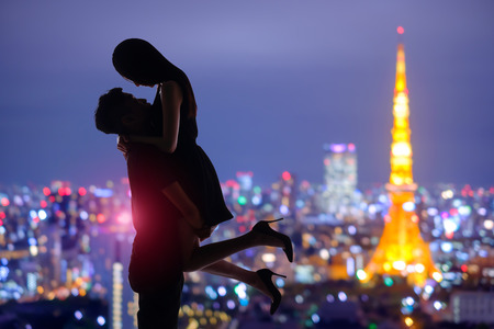couple lit: silhouette of romantic lovers with tokyo tower in japan with sunset