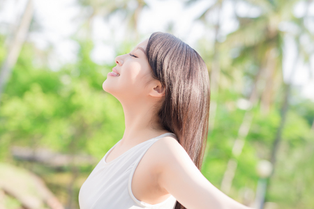 young woman raising her arms and smile to you, nature green background