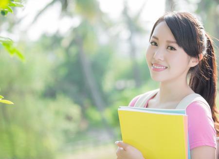 jeune femme étudiant sourire à vous. nature fond vert Banque d'images