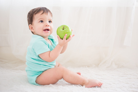 baby sit: cute baby boy take  green apple sit on the white bed in bedoom, caucasian Stock Photo
