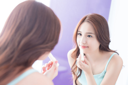 a young woman is  painting  lip balm in bathroom at home