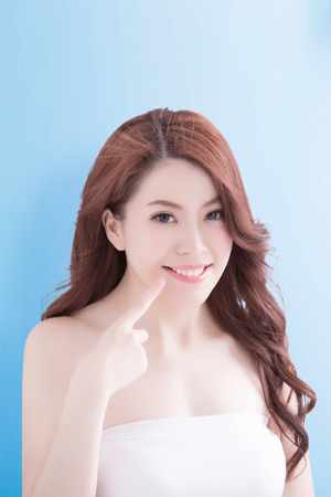asia women: Beautiful young woman with health teeth and charming smile. Isolated over blue background, asian beauty